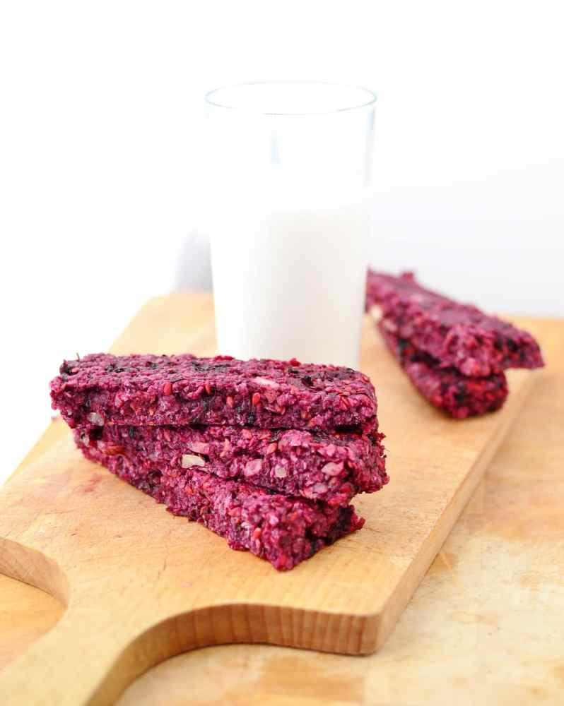 Blackberry breakfast bars on top of wooden board with glass of milk.