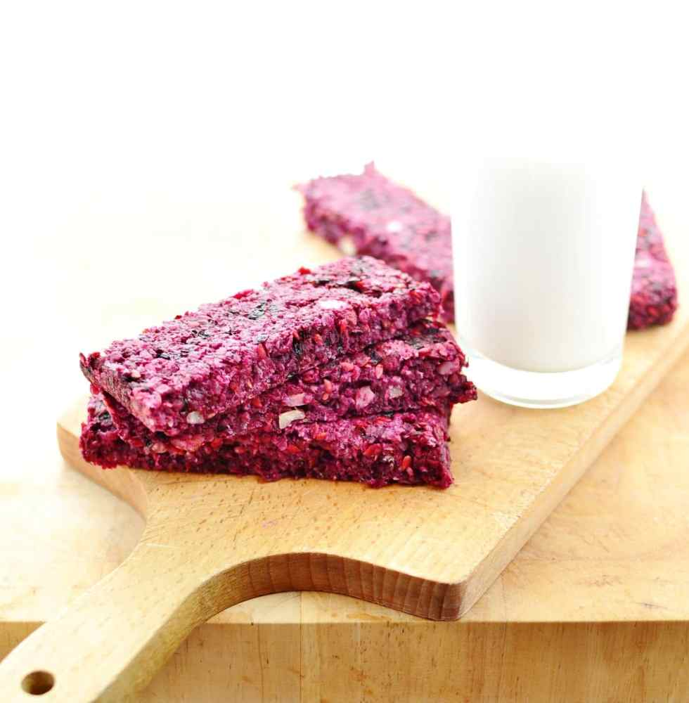 Blackberry oat bars on top of wooden board with glass of milk.