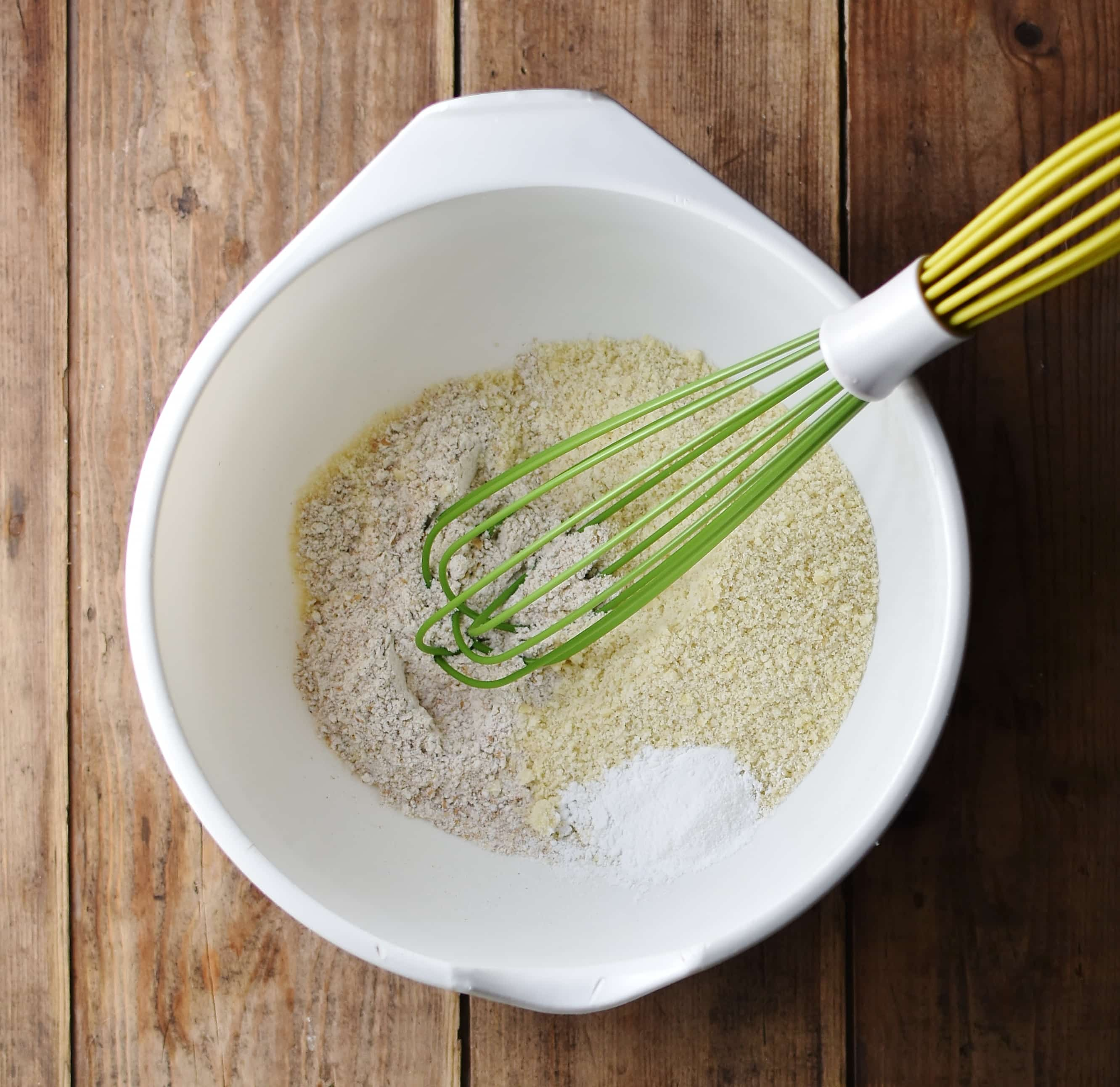 Flour mixture with green whisk on large white bowl.
