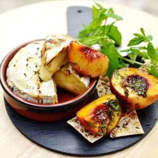 Baked camembert in round brown dish, with halved peaches, crackers and herbs on top of small slate platter.