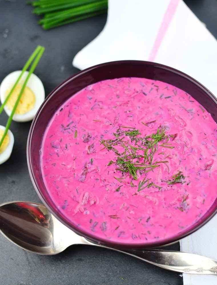 Top down view of cold beet soup with dill in purple bowl with spoon at bottom, white cloth and chives at top and hard boiled eggs to left.