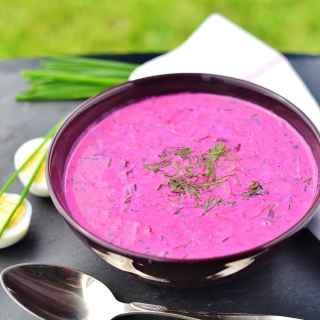 Cold beet soup in purple bowl with spoon in front, boiled eggs, chives and white cloth in background.