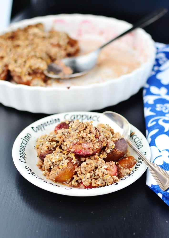 Side view of plum crumble on small white plate with spoon, blue-and-white cloth and white pie dish with crumble and spoon in background.