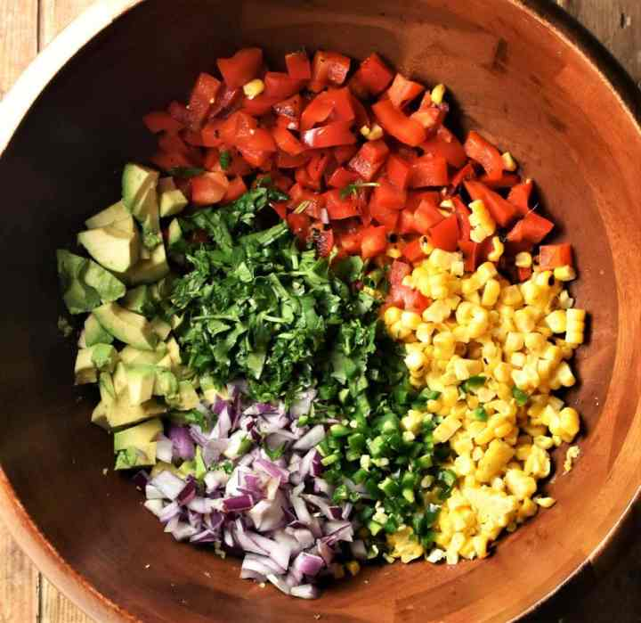 Corn and vegetable salsa ingredients in large wooden bowl.