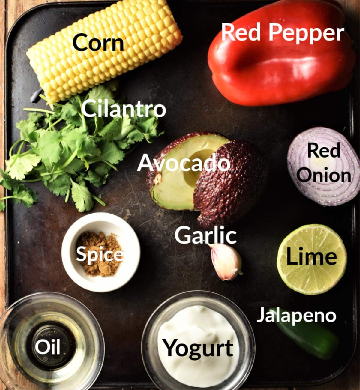 Corn salsa ingredients with labels in individual dishes on top of dark tray.