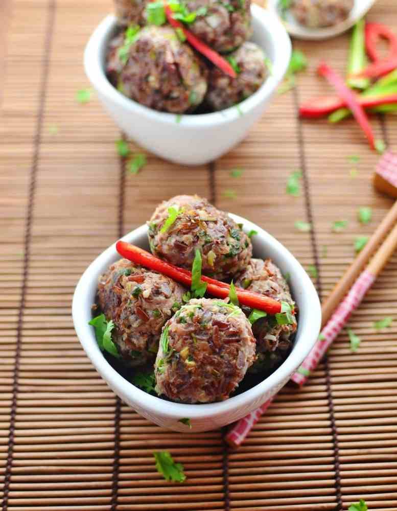 Turkey and rice meatballs with red chilli pepper inside small white bowls and in white spoons, with chopsticks, chopped herbs and chillies on top of bamboo mat.
