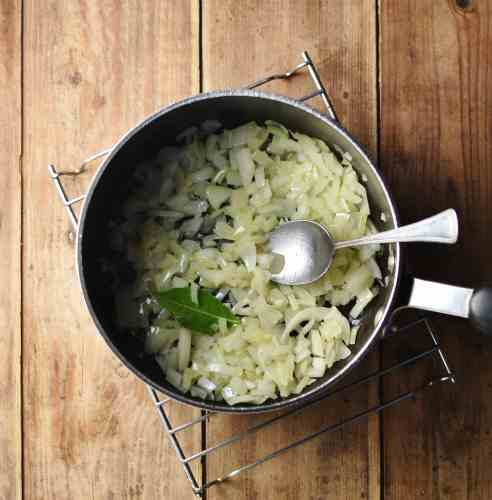 Chopped onions and bay leaf inside large pot with spoon.