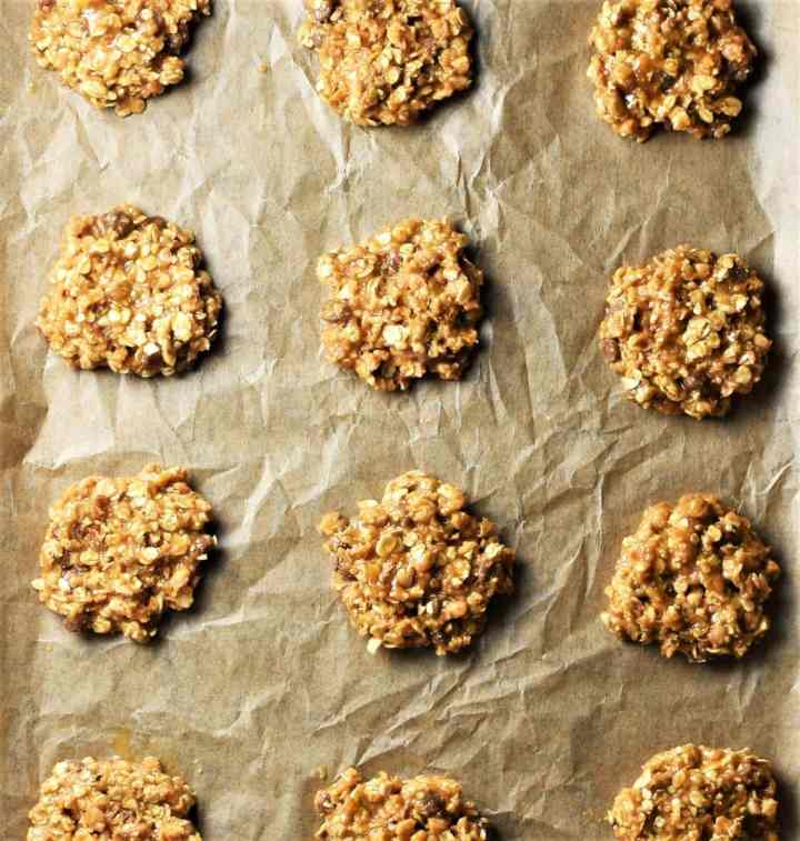 Unbaked oatmeal cookies on top of parchment.