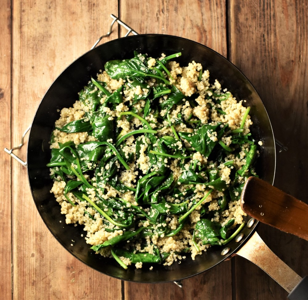 Wilted spinach and cooked quinoa in pan.