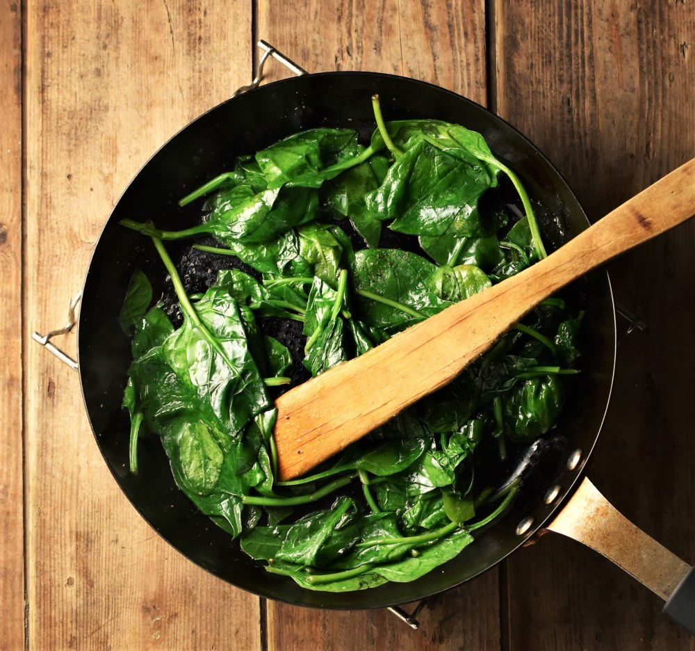 Spinach in pan with wooden spatula.