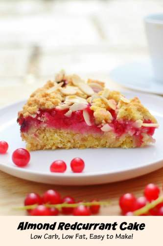 Side view of almond redcurrant cake slice on white plate with redcurrants on wooden surface.
