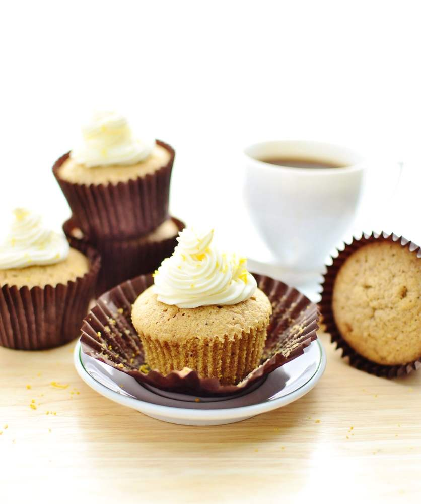 Cupcakes with cream cheese frosting in brown cases, one on top of white saucer, with white cup with coffee in background.