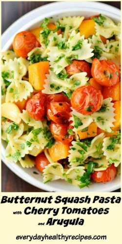 Top down partial view of farfalle pasta with cherry tomatoes, butternut squash pieces and herbs in white bowl.