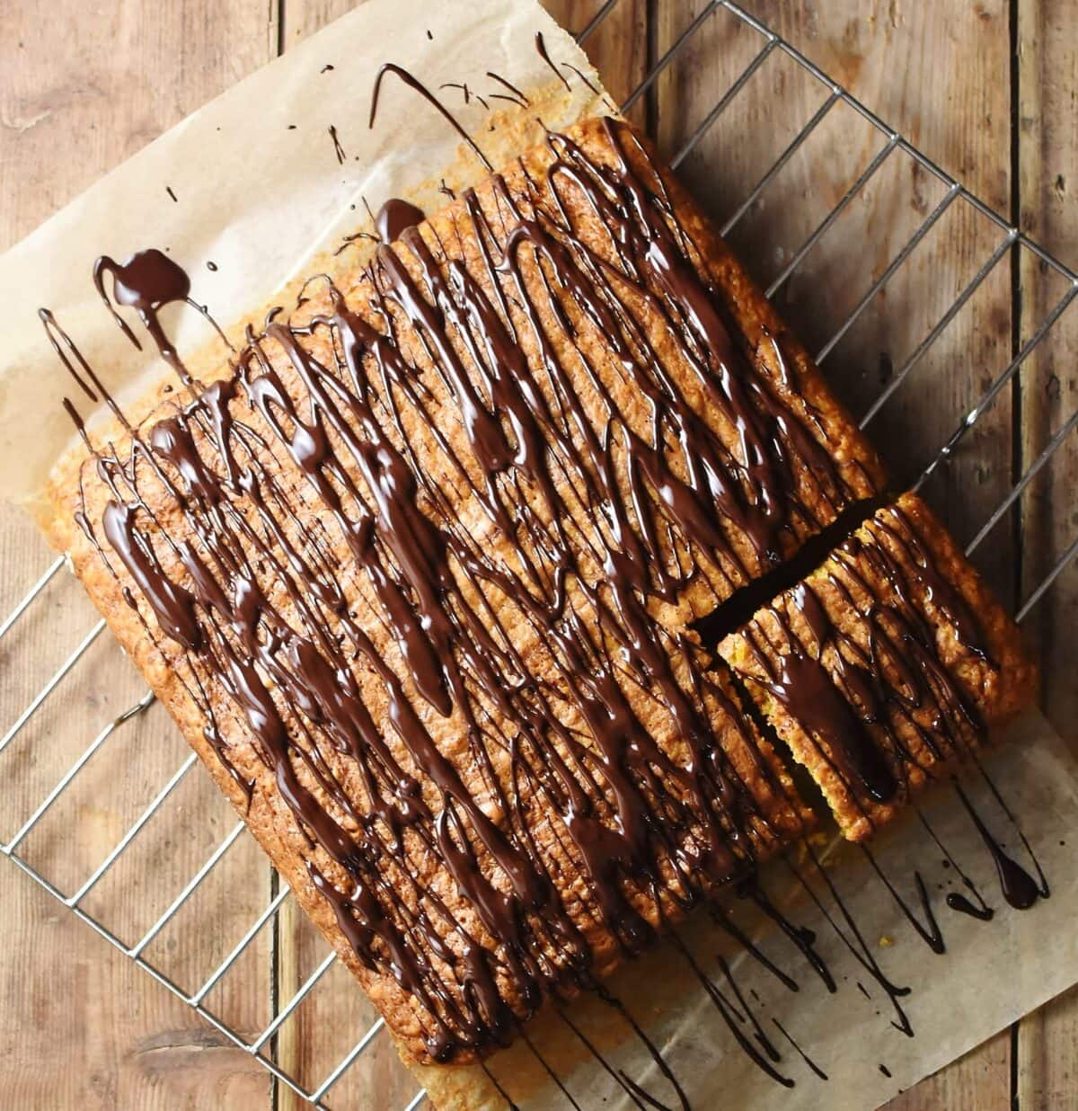 Square shaped cake with chocolate drizzle on top of parchment paper.