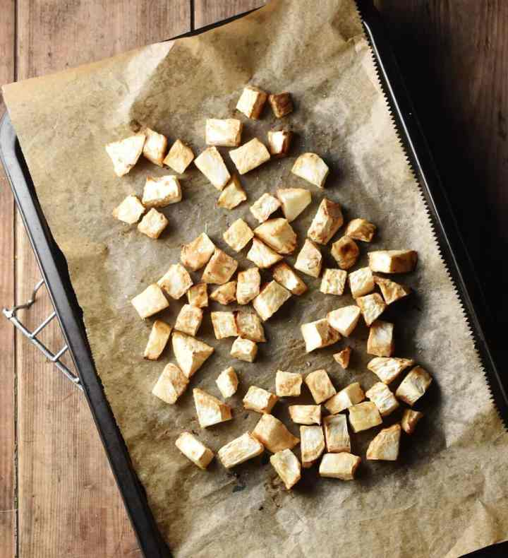 Cubed roasted celeriac on top of baking sheet lined with parchment paper.