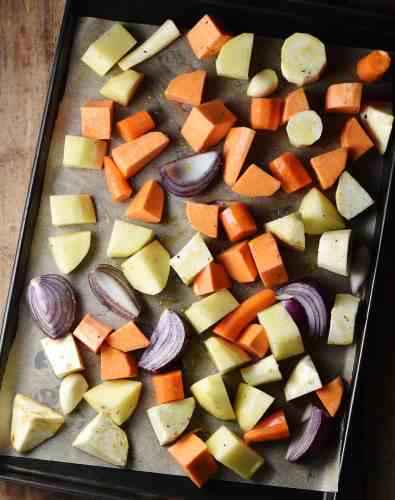 Chunks of peeled root vegetables and red onions on baking sheet lined with paper.