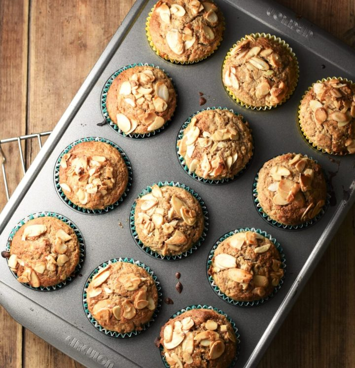 12 apple muffins with almond flakes on top in muffin pan.