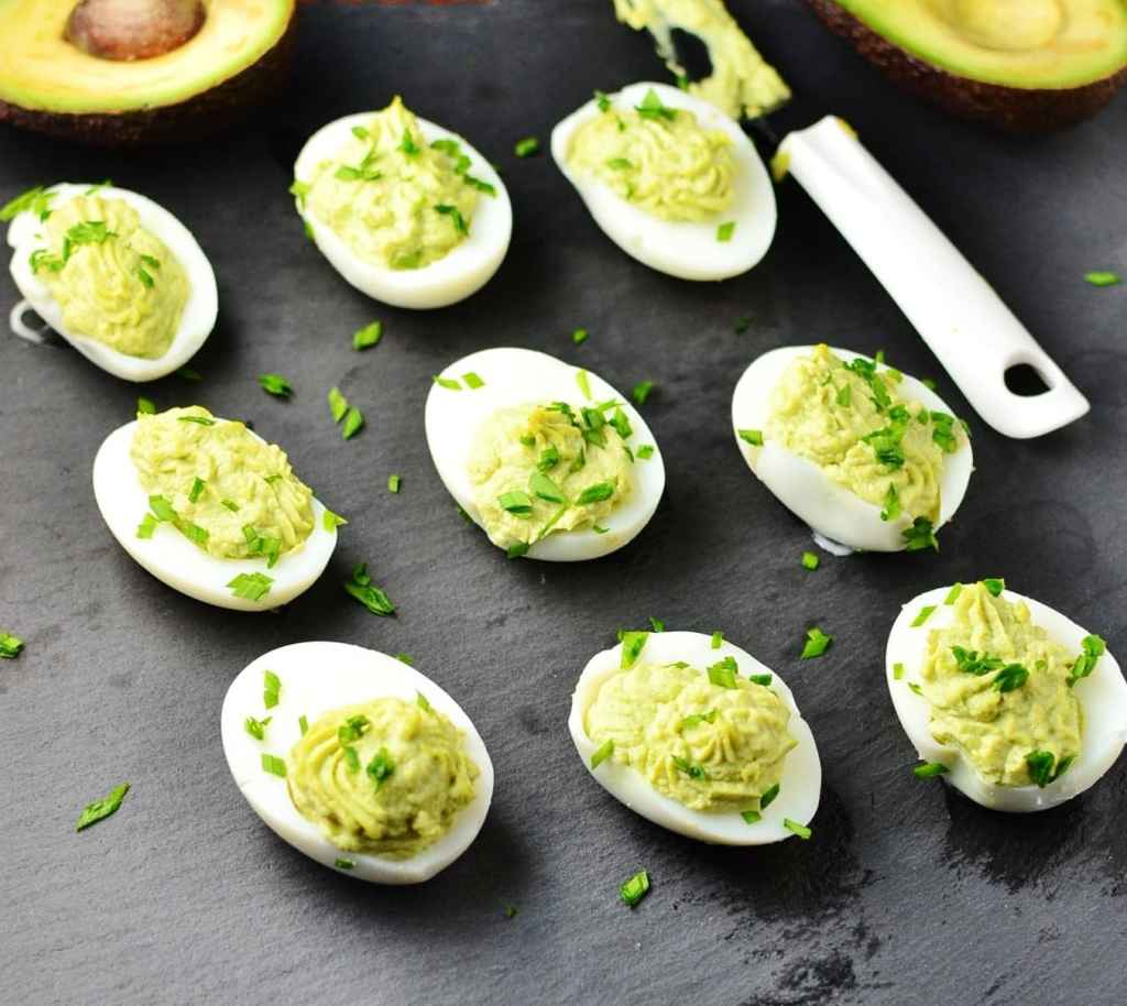 Deviled eggs with avocado and garnish of chives, halved avocado and white knife on dark grey surface.