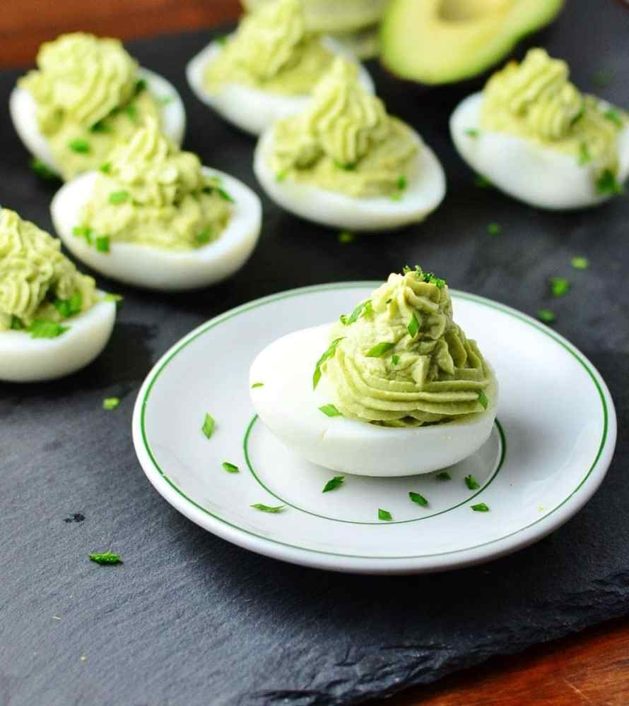 Deviled eggs with avocado and garnish of chives on white plate on top of grey surface.