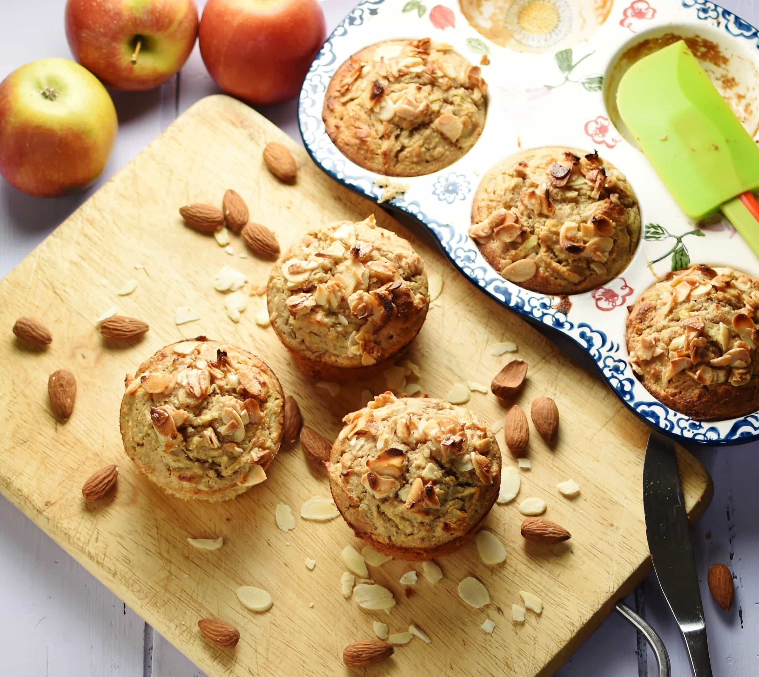 3 muffins with almond flakes on top with almonds on top of wooden board, with 3 more muffins inside ceramic muffin pan and apples in background.