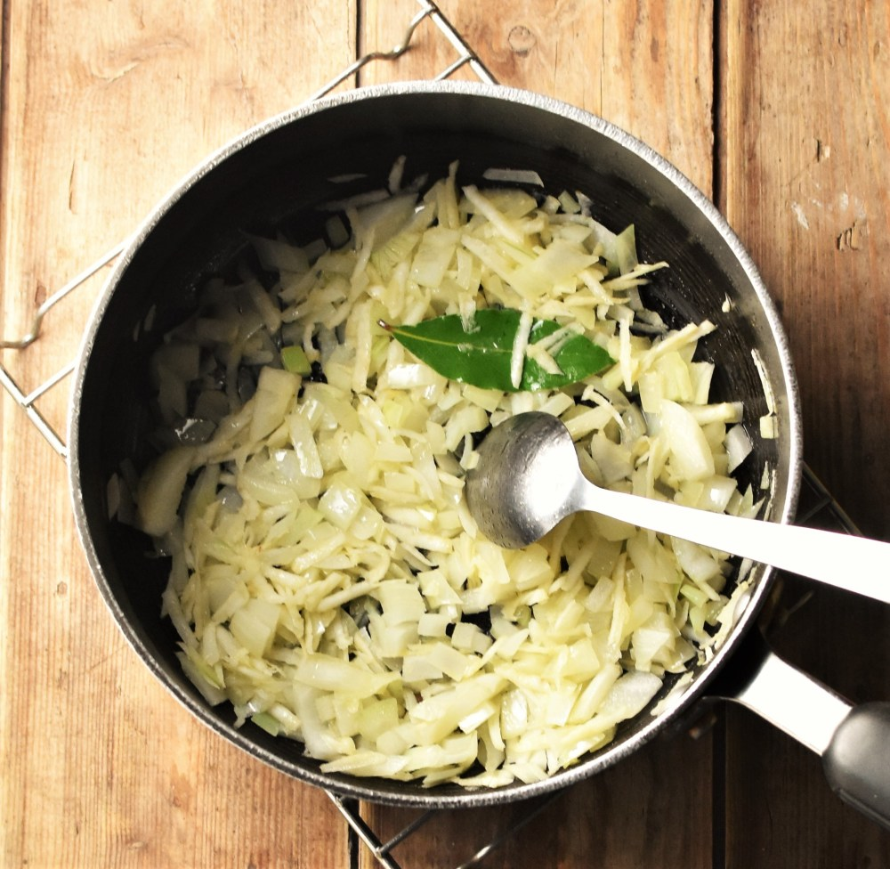 Chopped onion and bay leaf in large pot with spoon.