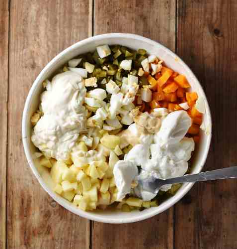 Chopped vegetables and yogurt inside large bowl with spoon.