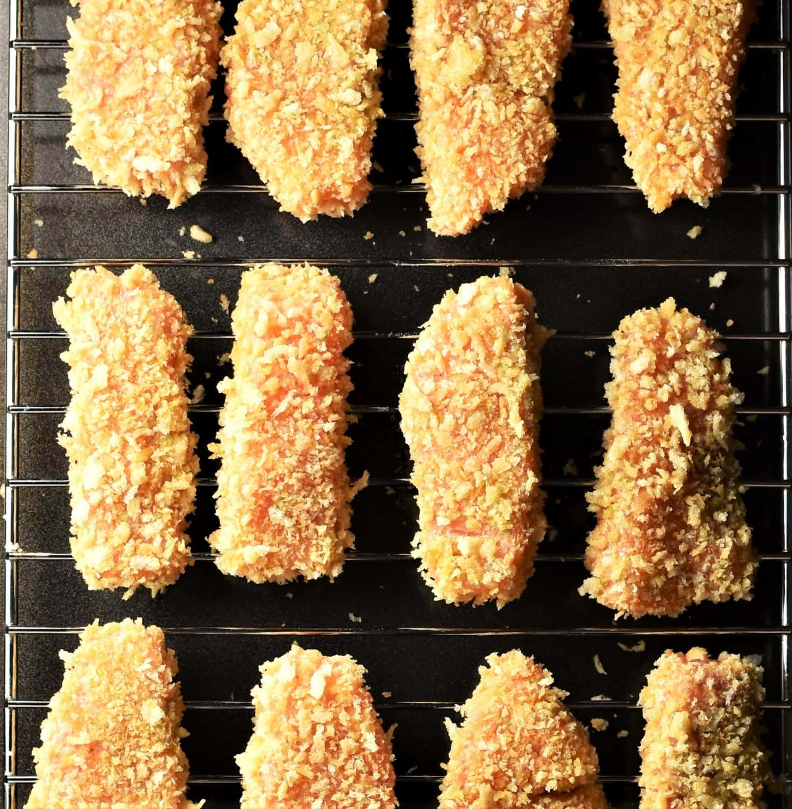 Unbaked breaded salmon pieces on top of rack.