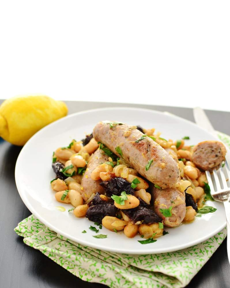 Side view of sausage and cannellini beans with prunes on top of white plate with fork, with green cloth and lemon in background.
