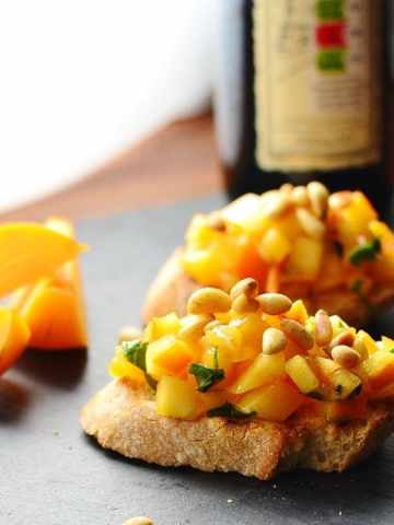 Chopped persimmon and pine nuts on top of 2 baguette slices with bottle in background and persimmon wedges to the left.