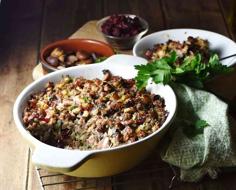 Side view of stuffing in white casserole dish, with green cloth, stuffing in white bowl and chestnuts in brown dish in background.