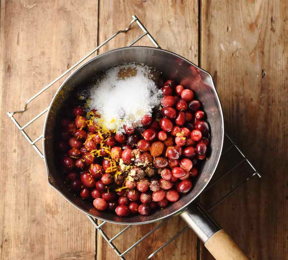 Cranberries with sugar and spice in saucepan.