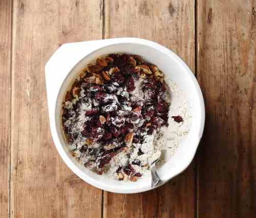 Dried cranberries, pecans and flour in white bowl with spoon.