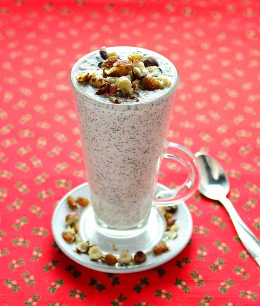 Side view of poppy seed raisin overnight oats topped with raisins and nuts in tall glass on top of saucer, with spoon on top of red cloth with hollies pattern.