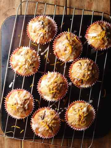 Muffins with icing and orange zest on top of rack.