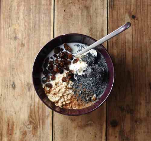 Poppy seeds, yogurt, oats and raisins in purple bowl with spoon.