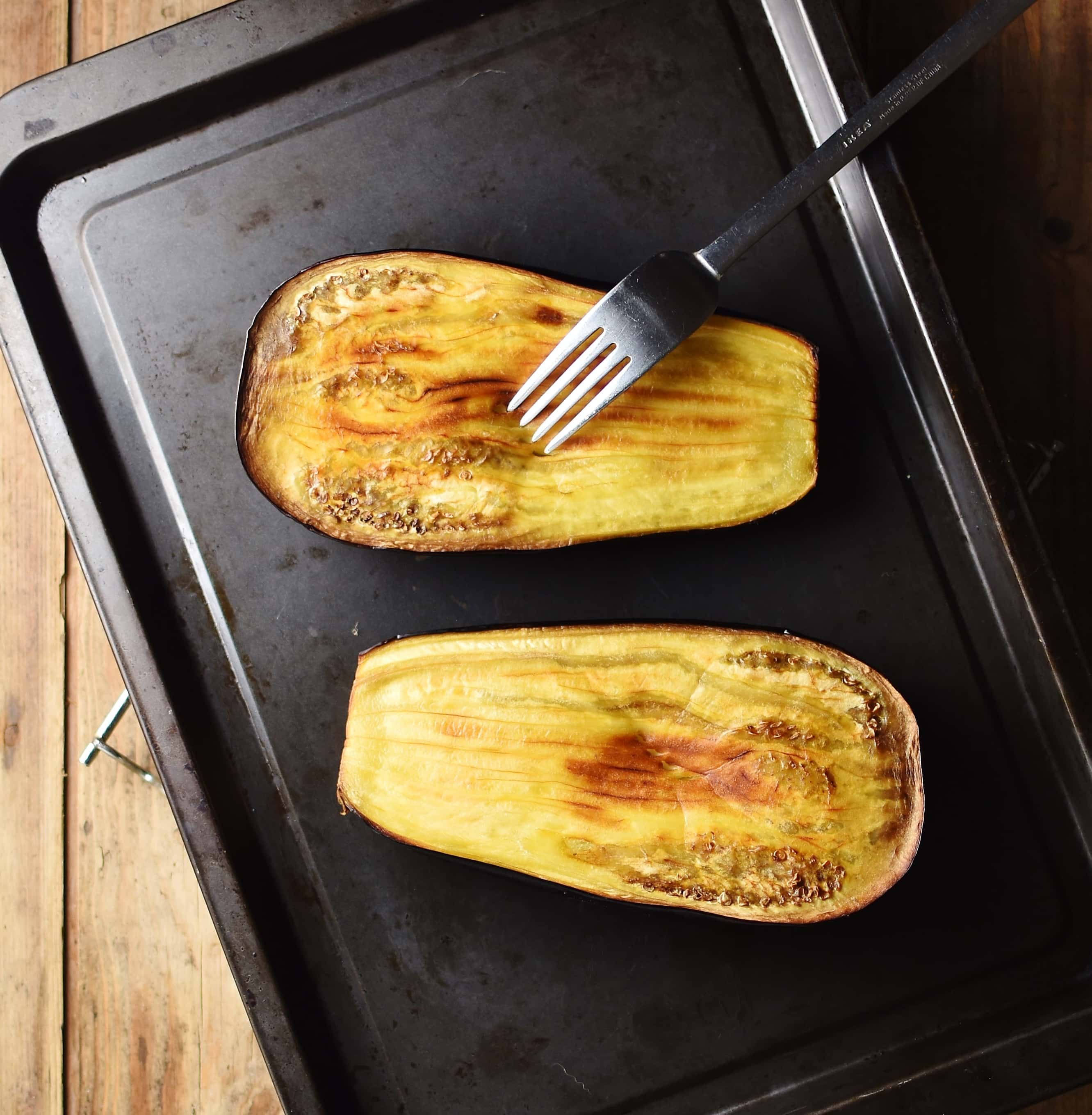 Roasted eggplant halves with fork on top of dark tray.