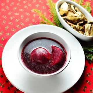 Beetroot soup with beetroot pieces in white bowl on top of white plate with spoon to the right.