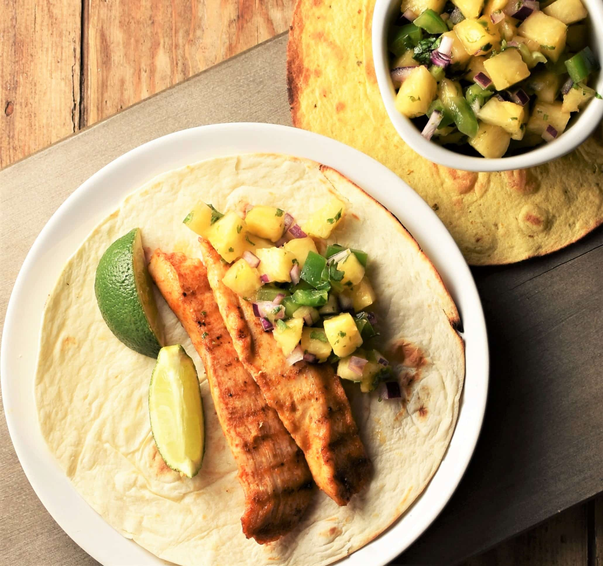 2 strips of grilled chicken with lime wedges and pineapple salsa in open tortilla with salsa in top right corner.