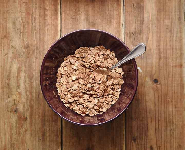 Oats with cocoa and soon in purple bowl.