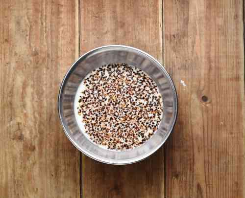 Coffee granules with milk in metal bowl.