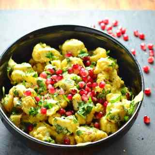 Curried cauliflower salad with yogurt dressing and pomegranate seeds in black bowl on top of grey surface.