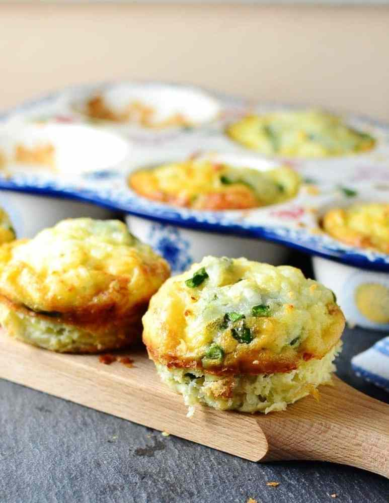 Asparagus frittata muffins on wooden board with white-and-blue muffin dish in background.