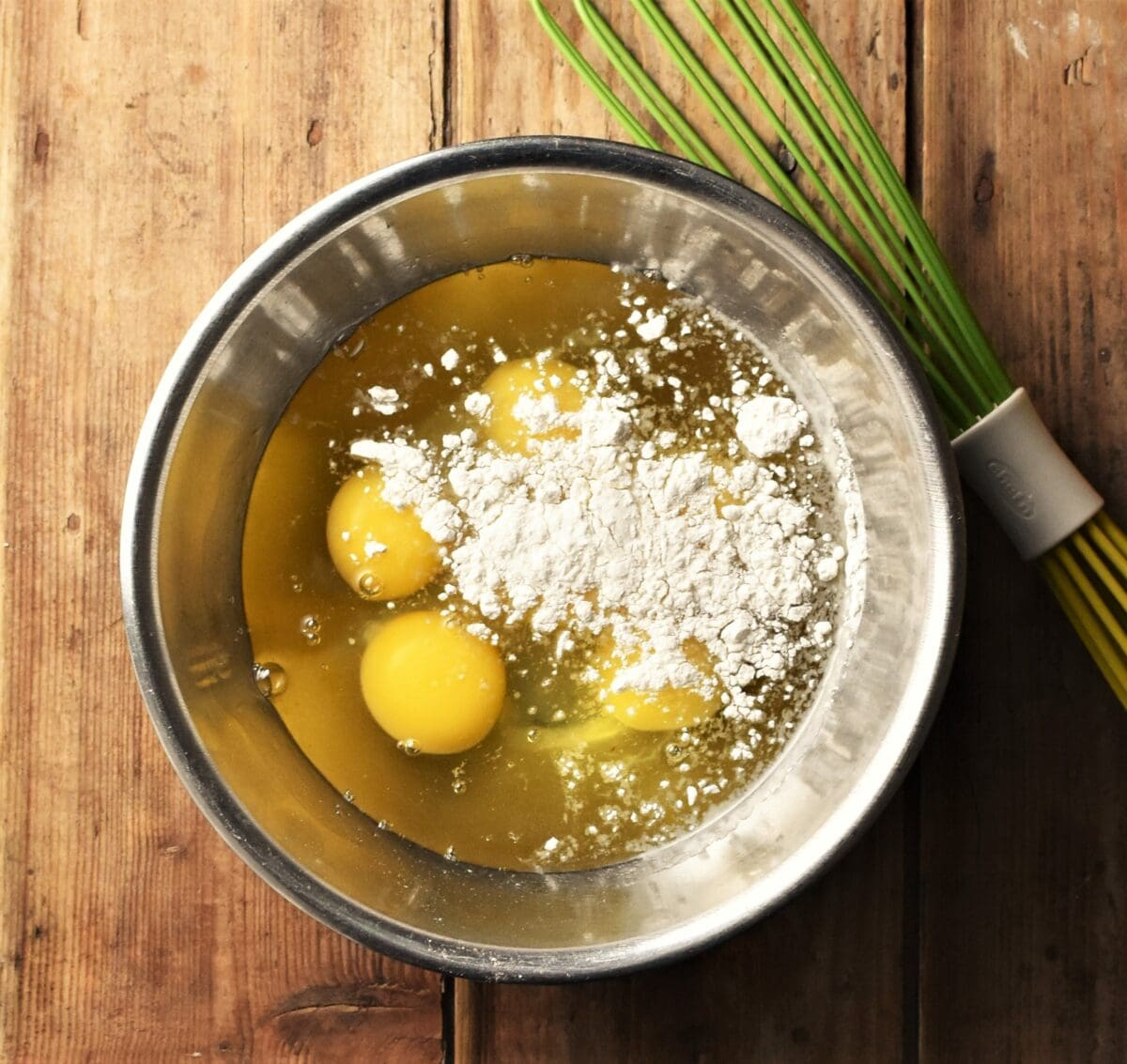 Raw eggs and a bit of flour in metal bowl with green whisk in top right corner.