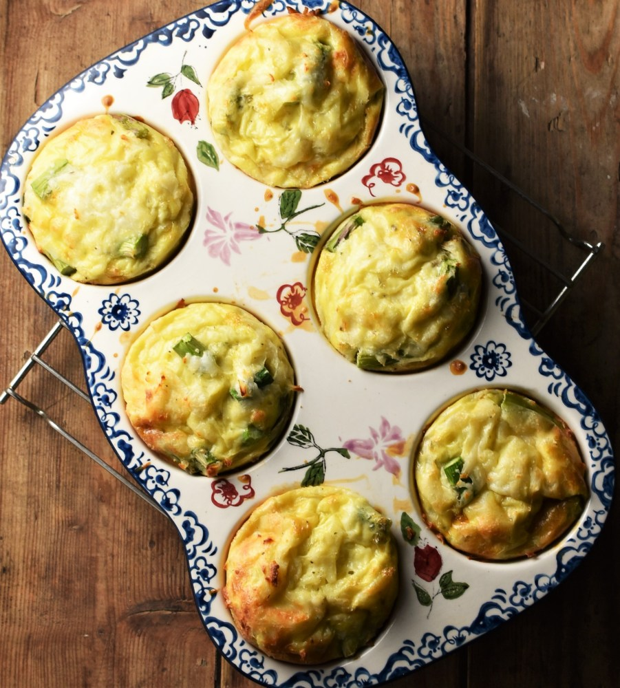 6 egg muffins in white ceramic muffin pan with blue flowery pattern.