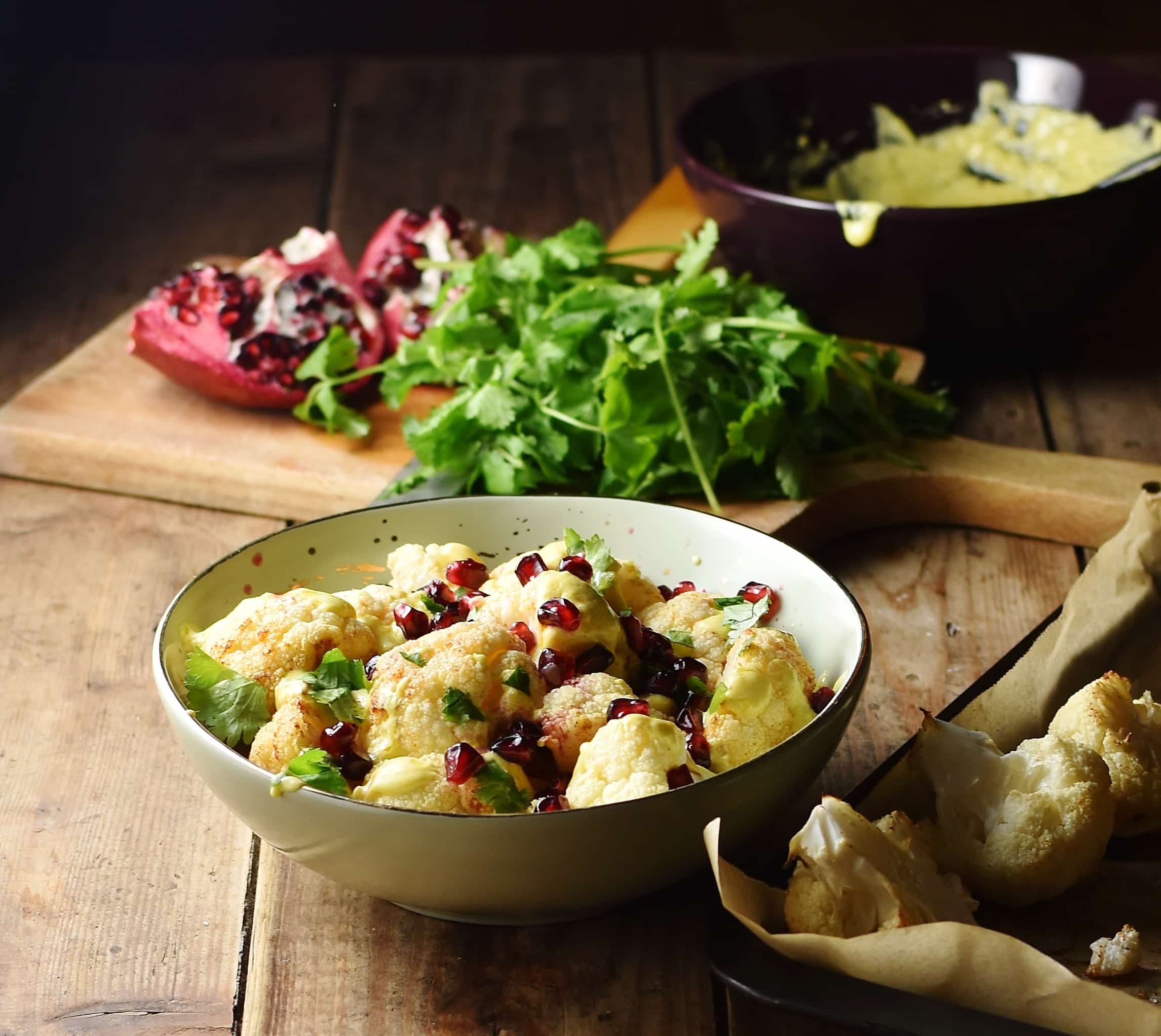 Side view of cauliflower salad with pomegranate seeds in yellow bowl with roasted cauliflower to the right, fresh herbs, pomegranate and creamy dressing in bowl in background.