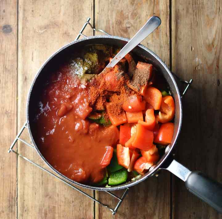 Chopped red pepper, tomatoes and spices in large pot with spoon.