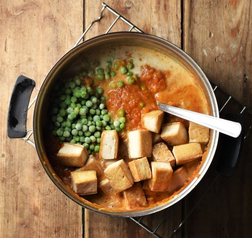 Cubed tofu, peas and tomato sauce in pot with spoon.