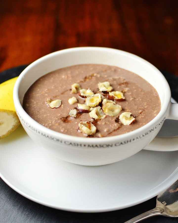 Mocha overnight oats in coffee cup on top of saucer with half banana in background.