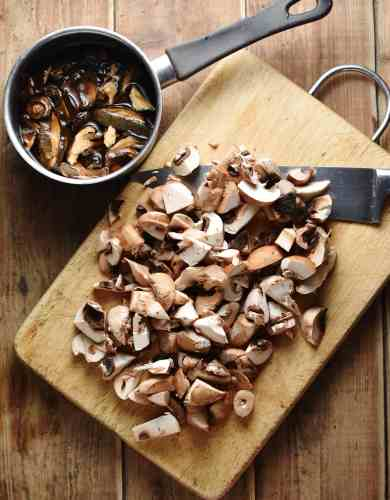 Top down view of chopped mushrooms with knife on top of cutting board and mushrooms in saucepan.