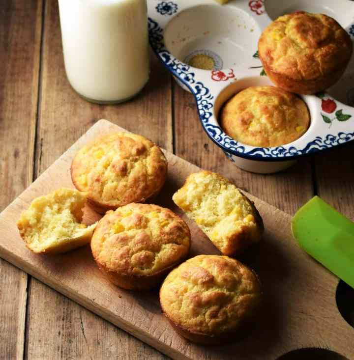 Corn muffins on top of wooden board with milk in bottle, muffins in ceramic pan and green spatula in background.